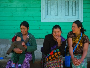 Mothers wait outside of a community center to have their baby's height and weight monitored to check for proper growth and development